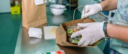 Unrecognizable cook packing a takeaway food order in the kitchen