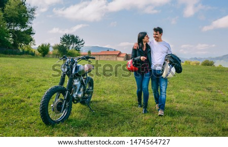 Unrecognizable couple walking on the field embraced and parked motorbike #1474564727