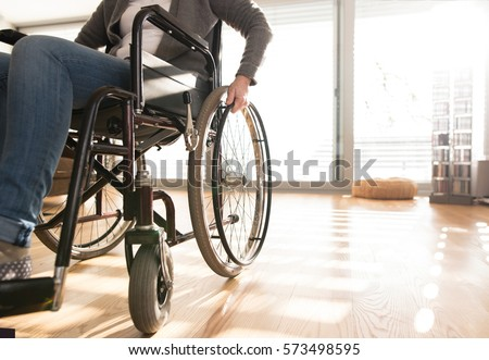 Unrecognizable disabled senior woman in wheelchair at home.