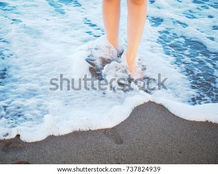 Unrecognizable female person walking alone in spuming sea water on a beach barefoot #737824939