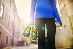 Unrecognizable female runner carrying her running shoes and bottle of water in old city center