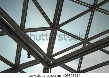 Unrecognizable fragment of modular / structural glass ceiling against sky. Glazed aluminum structure with triangular pattern. Abstract architectural background composition.