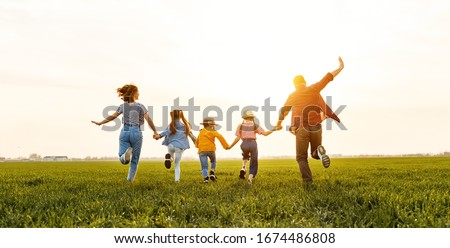 Unrecognizable happy   parents with daughters in casual clothes running back with holding hands while enjoying time together on green meadow in summer evening