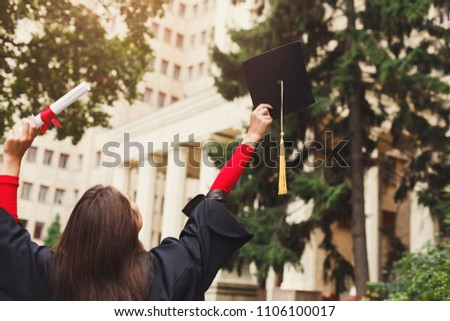 Unrecognizable happy woman on her graduation day at university holding diploma and raising hands, back view, copy space. Education, qualification and gown concept.