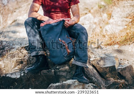 Unrecognizable hiker man looking for something in backpack on nature. Hiking and recreation theme