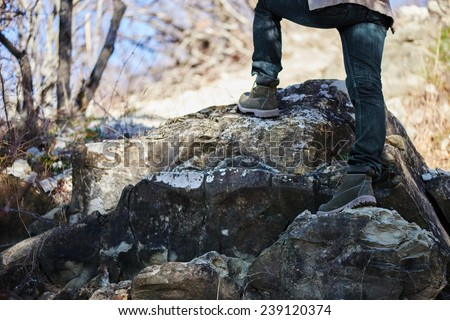 Unrecognizable hiker woman go up on rock, view of legs. Hiking and recreation theme