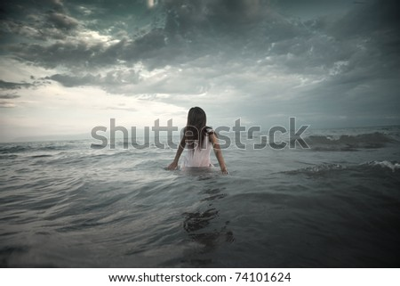 Unrecognizable human with face covered by hairs in the deep cold water.