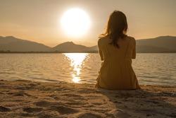 Unrecognizable lonely pensive woman sitting on the sand of seashore looking at the setting sun with light reflection in the water and orange sepia vintage photography effect. Dreaming person at dawn