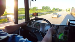Unrecognizable lorry driver holding hands on steering wheel and controlling his truck riding to destination. Close up steering wheel and dashboard of truck. View on traffic from inside cabin. Slow mo