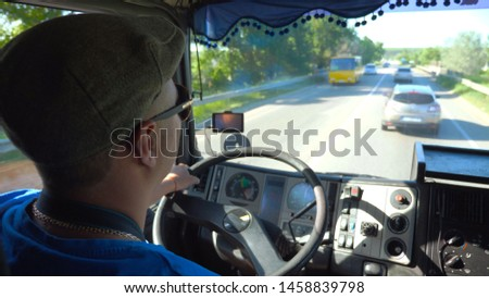 Unrecognizable lorry driver riding on county road at sunny day. Man in cap and sunglasses controlling his truck attentive watching road. View of traffic from inside cabin. Inside shot Slow mo Close up