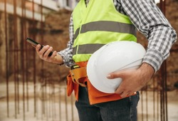 Unrecognizable male builder with helmet browsing mobile phone during break in work on construction site