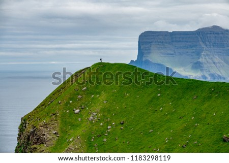Unrecognizable male hiker stands on the grassy hill in the distance and takes photos of breathtaking fjords in Faroe Islands. Beautiful shot of tiny man in the magnificent Scandinavian countryside.