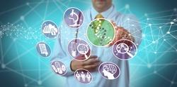 Unrecognizable male scientist using a pharmacogenomics platform in drug discovery. Concept for pharmaceuticals, bioinformatics, pharmacogenetics, DNA, biochemistry, pharmacology, genetic makeup.