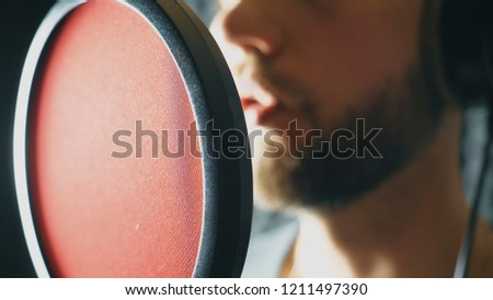 Unrecognizable male singer singing in sound studio. Man recording new song. Guy with beard sings to microphone. Working of creative musician. Show business concept. Slow motion Close up. #1211497390