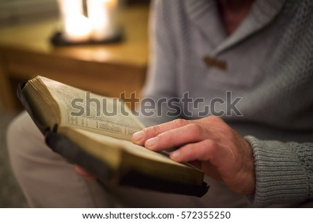 Unrecognizable man at home reading Bible, burning candles behind
