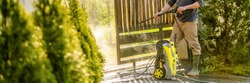 Unrecognizable man cleaning a wooden gate with a power washer. High pressure water cleaner used to DIY repair garden gate. Web banner.