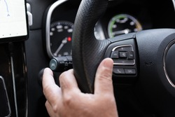 Unrecognizable man driver activating the adaptive cruise control or steering assistant on the control stick behind steering wheel  in electric vehicle - EV. Driving Assist system in modern car.