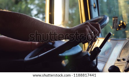 Unrecognizable man holding his hands on steering wheel and driving car at country road on warm summer day. Truck driver rides to destination. View from the lorry cab. Slow motion Close up #1188817441