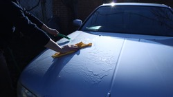 unrecognizable man in dark clothes washes the silvery surface of the car with water from a hose using a yellow suede cloth to wipe the metal, waves of water spread textured over the metallic hood