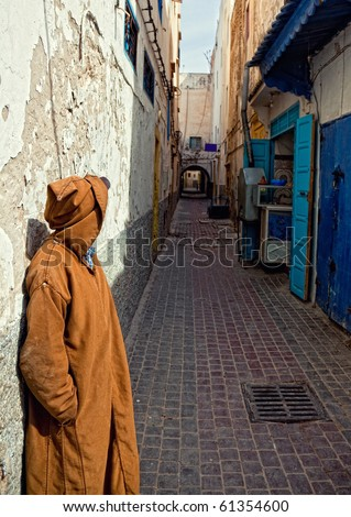unrecognizable man in djelleba standing at the old arabic street photo