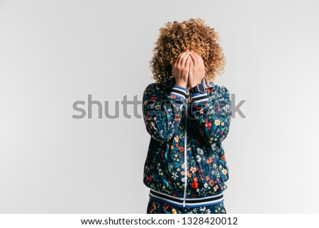 Unrecognizable man in fashionable modern tracksuit with flowers and afro hairstyle hidng  face with hands. Indoor portrait of unknown male depressed crying person. Isolated on white guy feeling shame