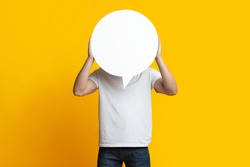Unrecognizable man in jeans and white t-shirt hiding behind empty communication bubble over yellow studio background. Guy showing huge white blank clipart, copy space, communication, chatting concept