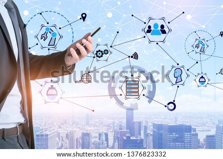 Unrecognizable man in suit looking at smartphone over city background with double exposure of GUI interface and network hologram. Concept of hi tech in business. #1376823332