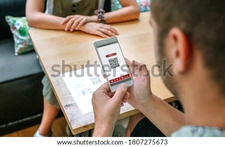 Unrecognizable man scanning restaurant menu QR code on table