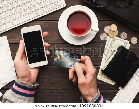 Unrecognizable man shopping online with credit card and laptop, sitting at office, e-commerce concept, copy space #1091850896