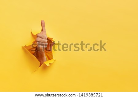 Unrecognizable man shows like gesture through torn yellow wall, keeps thumb up, says you are best, demonstrates approval sign, recommends something. Copy space aside for your advertising content
