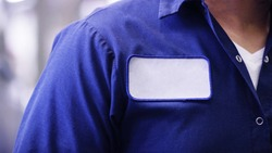 unrecognizable man wearing blue uniform shirt with empty name white tag or patch, worker or employee Identification.