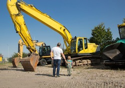 Unrecognizable man with his son on a sunny summer day stand side by side, holding hands, looking at large yellow crawler excavators. The boy's hobby for construction equipment
