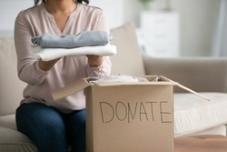 Unrecognizable mixed-race woman cropped image close up view sit on couch near donation box holding clothes taking part at humanitarian aid organization help to needy. Old belongings charity concept