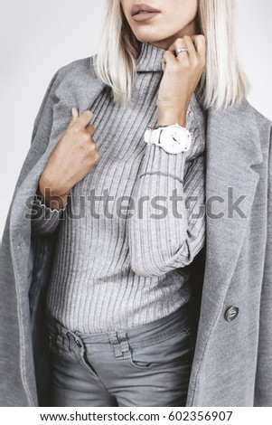 Unrecognizable model wearing casual outfit. Gray clothing in trendy minimalistic style. Street fashion for spring or fall season. Details of everyday elegant look.