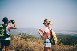 Unrecognizable multiethnic travelers wearing summer clothes and sunglasses with backpacks standing on hill and photographing landscape with mobile phone in sunny day