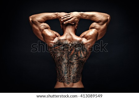 Unrecognizable muscular man with tattoo on back against of black background.Isolated.