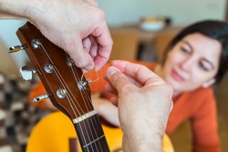 Unrecognizable music male teacher changing guitar strings. Detail of woman learning step by step instructions to properly tune guitar strings. Music course online concept. Indoor lifestyles.