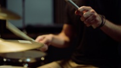 Unrecognizable musician hands hitting drum plates in recording studio. Close up of drummer hands performing solo with drumsticks. Attractive artist playing on drum kit indoor.