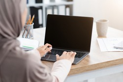 Unrecognizable muslim woman working on laptop with black screen, typing on keyboard, sitting in modern office, over shoulder view, mockup