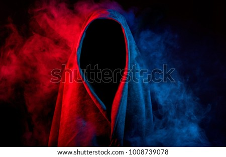 unrecognizable mysterious silhouette in cloak covered by colorful smoke on black background
