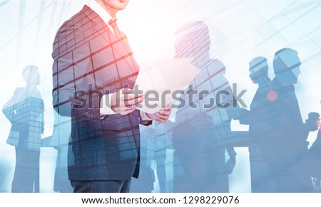 Unrecognizable pensive businessman with documents standing over skyscrapers background with double exposure of his colleagues. Leadership concept. Toned image