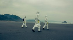 Unrecognizable people with bacteriological protection suits walking on the sand of the beach