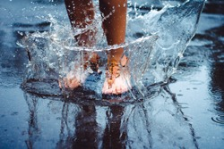 Unrecognizable person (female) is splashing water in a puddle on a rainy day in the city. Legs in puddle.