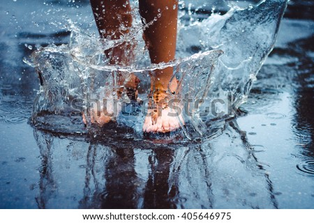Shutterstock Unrecognizable person (female) is splashing water in a puddle on a rainy day in the city. Legs in puddle.