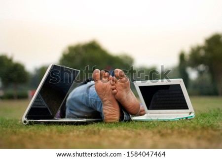 Unrecognizable person Laying Dawn in the Park After Working on Laptop #1584047464