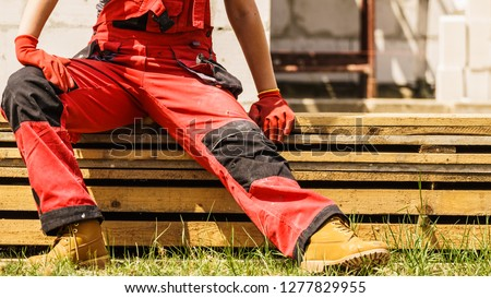 Unrecognizable person on construction site wearing protective worker red black pants trousers Stockfoto ©