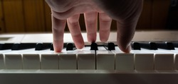 Unrecognizable person playing piano, creating music in his home studio