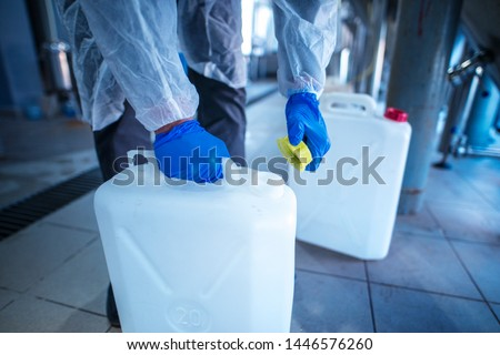 Unrecognizable person technologist in white protective suit handling acid or detergent in chemical industry. Industrial worker opening plastic canister to use chemicals. #1446576260