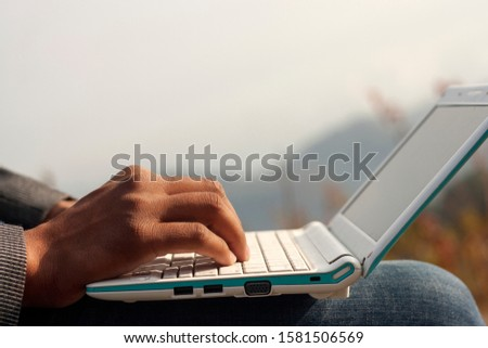 unrecognizable person using laptop outdoor in nature. #1581506569