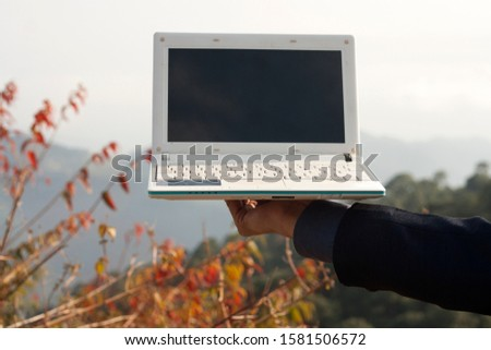 unrecognizable person using laptop outdoor in nature. #1581506572